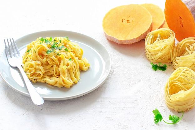 Тыквенные макароны альфредо феттуцин в керамической тарелке со свежими сырыми кусочками тыквы. осенняя еда на обед. рецепт тыквенного ореха.