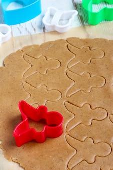Процесс работы с пряничным печеньем, использование красного пряничного человечка для резки пряничного теста на бумагу для выпечки вокруг красочных формочек на белом деревянном столе. вид сверху
