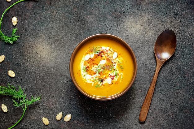 Жареный суп из тыквы и моркови со сливками, семенами и свежей зеленью в керамической миске. вид сверху