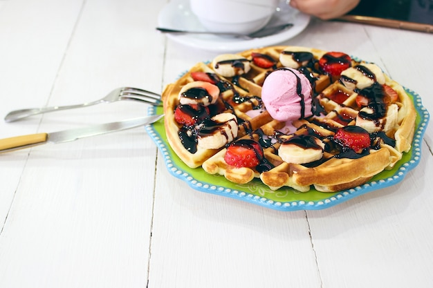 Молодая девушка, сидящая в кафе, завтракает вафлей с шоколадным соусом, кусочками банана и клубникой на зеленой керамической тарелке и фотографирует свой завтрак