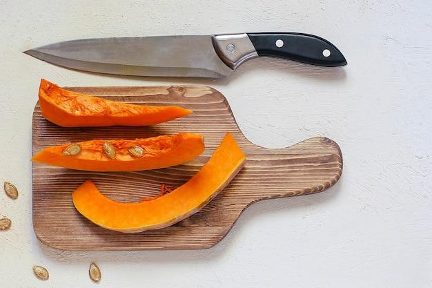 Жареный суп из тыквы и моркови со сливками, черным перцем и тыквенными семечками, разделочная доска и свежие кусочки тыквы, черный хлеб