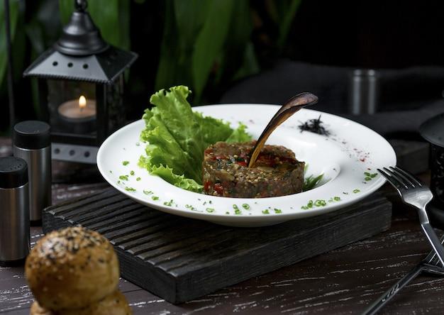 サラダの葉と丸い形のリブアイステーキ