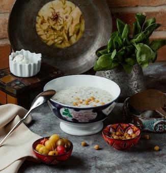 中に黄色い豆を入れた伝統的なヨーグルトスープのボウル、野菜のマリネ添え