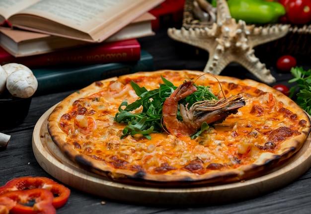 Вкусная пицца из морепродуктов с плавленым сыром, жареным крабом и зеленым салатом на вершине