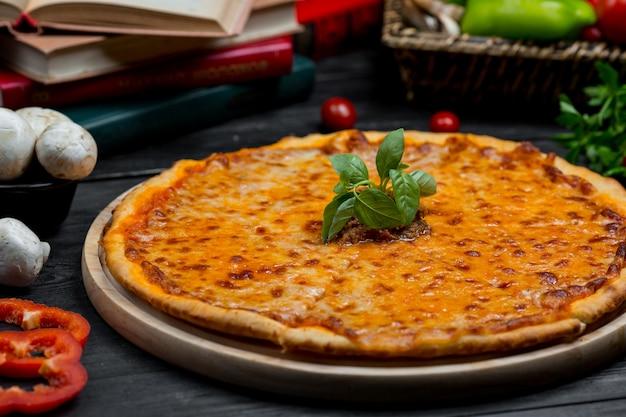 完全に溶けたチェダーチーズと新鮮なバシリカの葉が付いたクラシックなマルガリータピザ