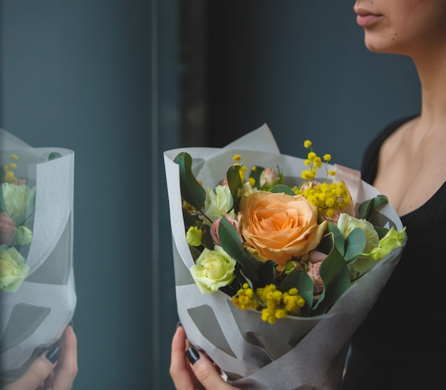 Женщина, стоящая перед окном и смотрящая снаружи с букетом коралловых роз в руке