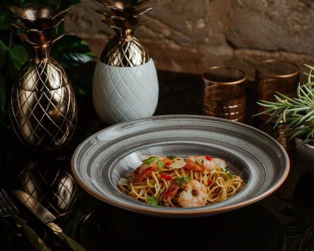 Спагетти, приготовленные с морепродуктами и свежими овощами и поданные в серой гранитной тарелке