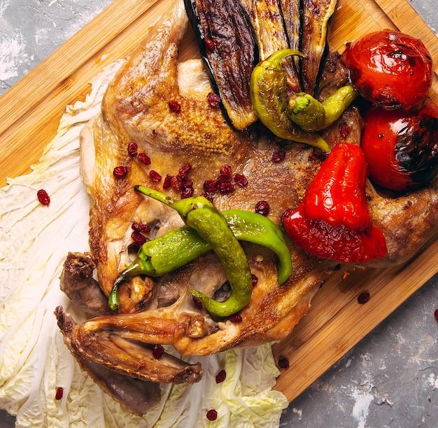 木の板のクローズアップで焼き鶏と野菜。上からの水平方向の図