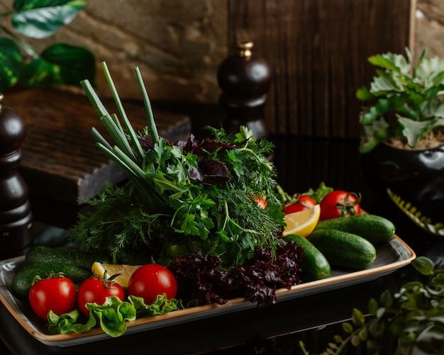 トマト、キュウリ、さまざまな緑を含む新鮮な季節野菜のプレート