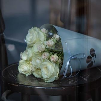 黒い木製の椅子の上に立っている白いバラの灰色の紙の花束