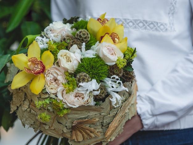 紙の花束の花の淡い色を保持している白いシャツの女性