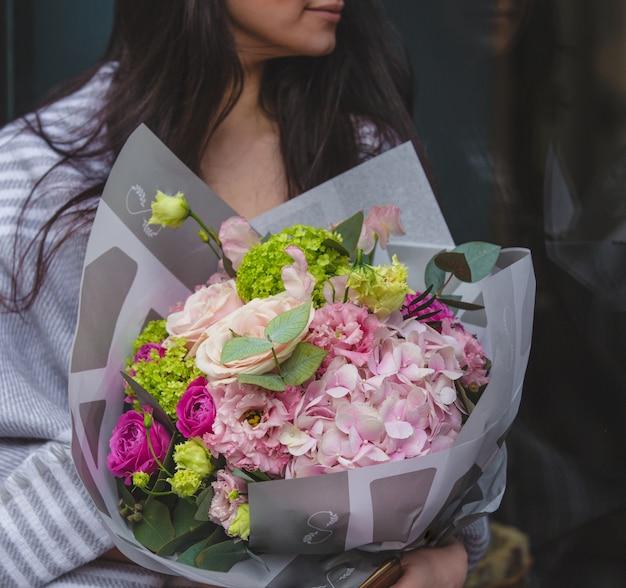 季節の花の花束を持って部屋に座っている女性