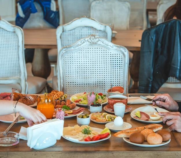 レストランで朝食用テーブルの周りに座っている人