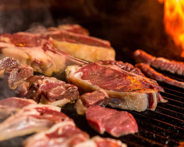 炎の横にあるグリルでステーキ料理