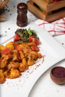 Кусочки говяжьего мяса в томатном соусе с луком и болгарским перцем. подается в белой тарелке с базиликом, черным перцем