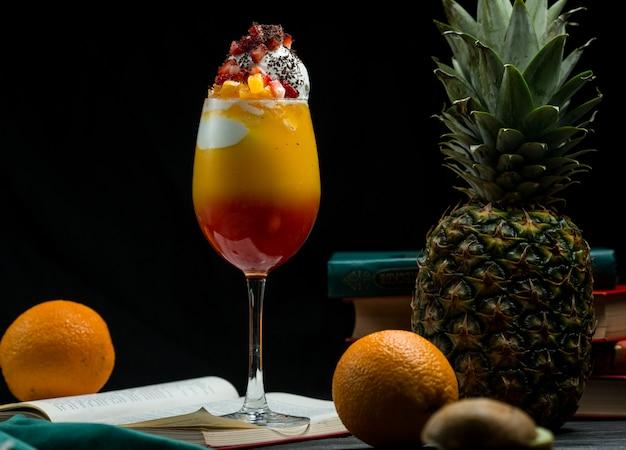 Стакан полного смешанного коктейля из тропических фруктов с насыщенными цветами, стоящего на книжных листьях