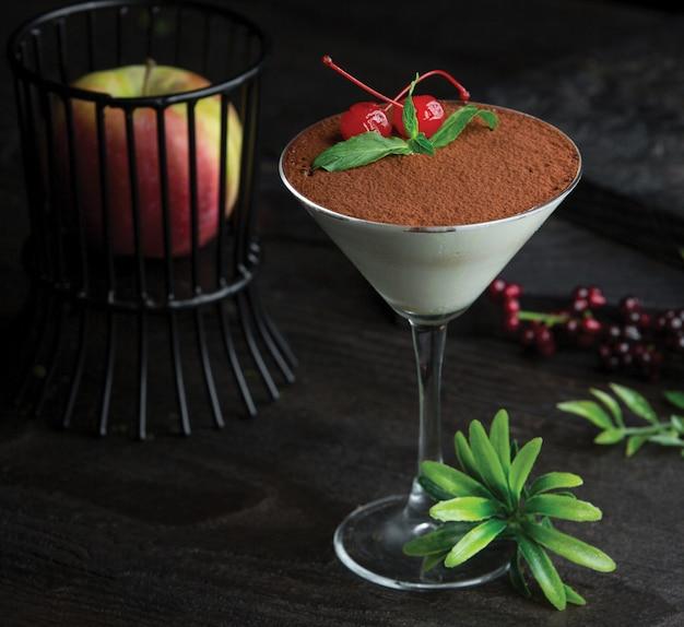 Бокал тирамису с какао и ягодами на вершине