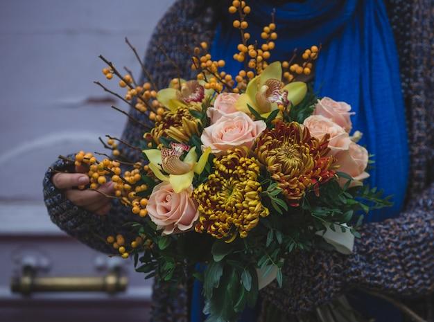 秋のコンセプトの花の花束とウールのセーターの女性