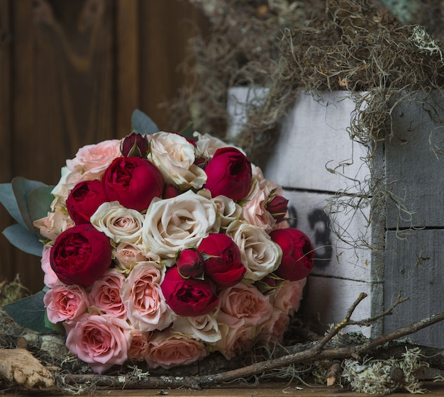 ドアの上に立っている深くて明るいピンクの牡丹の花束