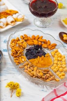 Чайный сервиз с традиционными орехами, лимоном, конфитюром и сладостями на белой скатерти
