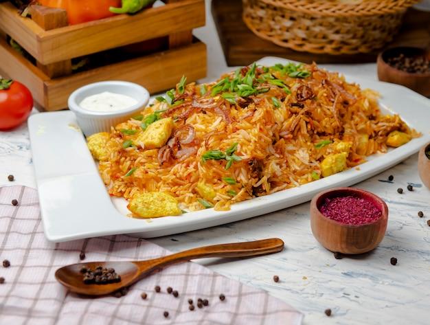 Куриная грудка, томатный соус рис, ризотто, плов с зеленью, йогурт и сумах в белой тарелке