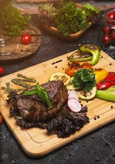 Клубный бифштекс с перечным соусом и овощами гриль на разделочной доске