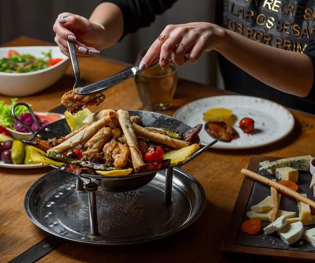 嚢の皿から肉の部分を取る女性