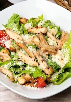 Салат цезарь с пармезаном и курицей, свежий салат, хлебные крекеры и помидоры черри в белой тарелке.