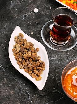 Маленькие сладкие леденцы-сусам в белой тарелке с персиковым конфитюром и турецким чаем.
