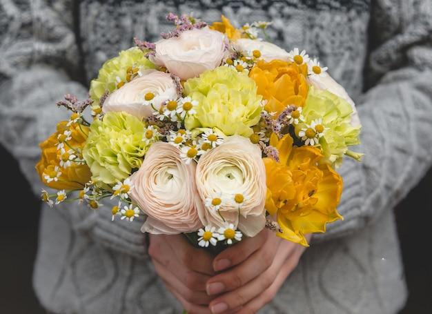 冬に黄色のトーンの花の花束を提供している男