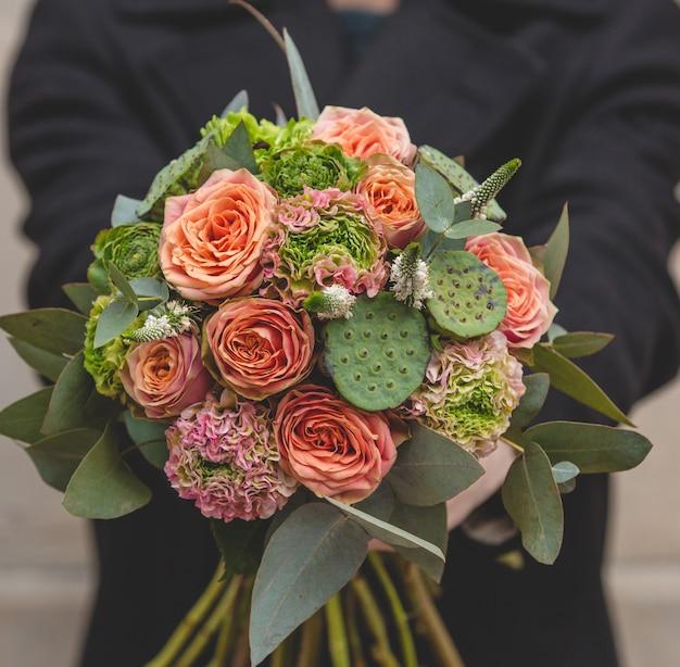 バラとサボテンの花束を持って男