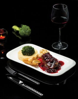 Тарелка стейка в соусе из красного вина и пюре из овощей