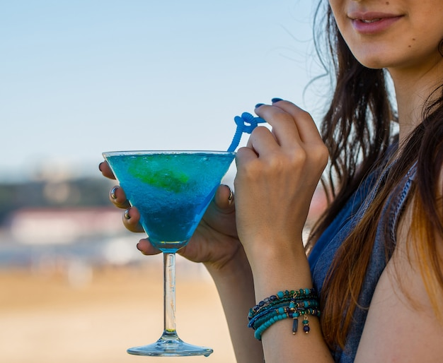 Девушка пьет голубой лагуны алкогольный коктейль с голубыми трубками