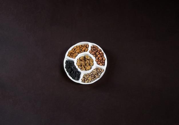 Вид сверху орехи пластины с сухофруктами на черном столе.