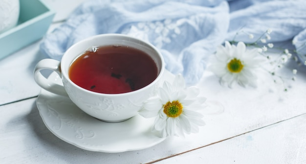 Белый фон, чашка чая и ромашки.