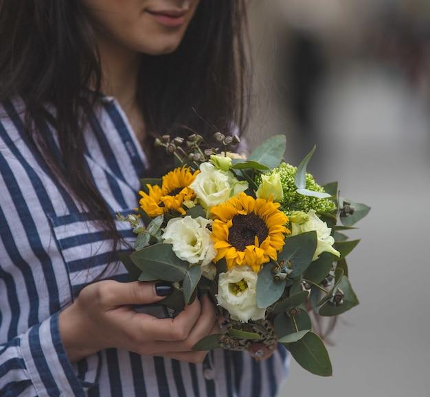 Девушке предлагается букет подсолнухов и белых роз