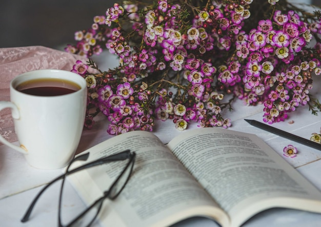 Счастливый уголок, живые цветы, чашка чая, книга и стаканы