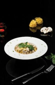 Паста с лапшой в сливочном соусе с базиликовыми листьями.