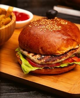 Бургер из куриного мяса с ломтиками помидоров и листьями салата, подается с картофелем фри, кетчупом и майонезом на деревянной доске