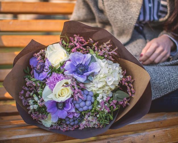 花の紙の花束とペンチに座っている女性。