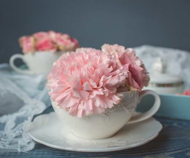 白いカップの上にピンクの花を置きます。