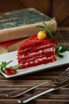 上部にイエローチェリーとミントの葉の赤いベルベットケーキスライス