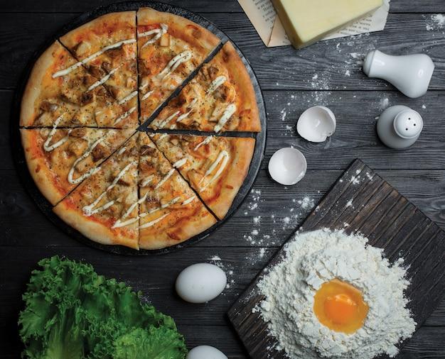 ピザを牧場ソースでスライスし、小麦粉と卵で生地を作る