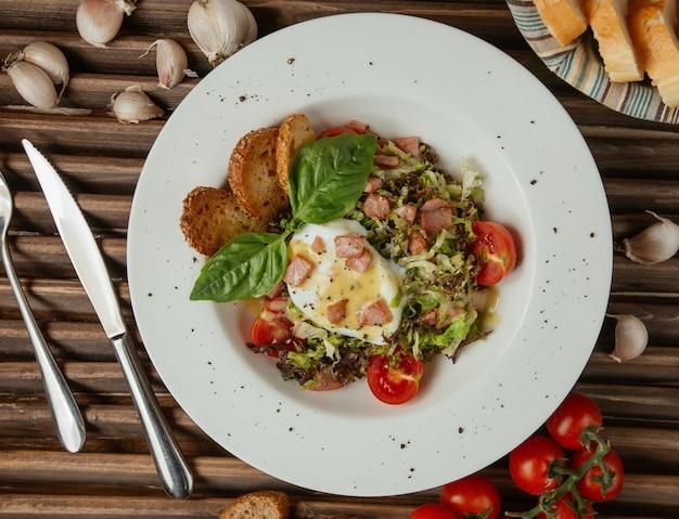 Вид сверху жареное яйцо в белой тарелке с зеленым салатом