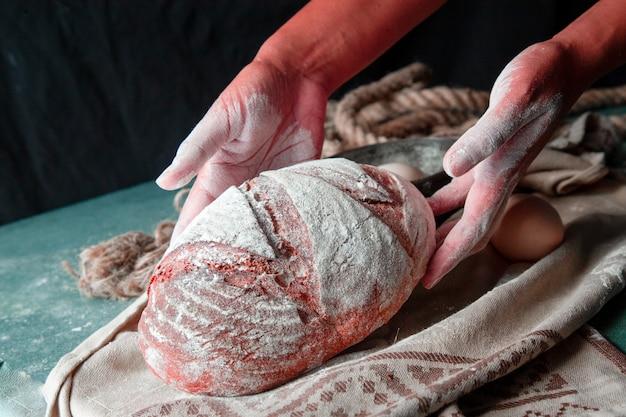 茶色のタオルに手で全体の自家製パンを置く女性。パンの上に小麦粉。