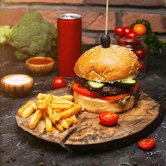 Домашний гамбургер макро с говядиной, помидорами, листьями салата, сыром и картофелем на разделочной доске. быстрое питание