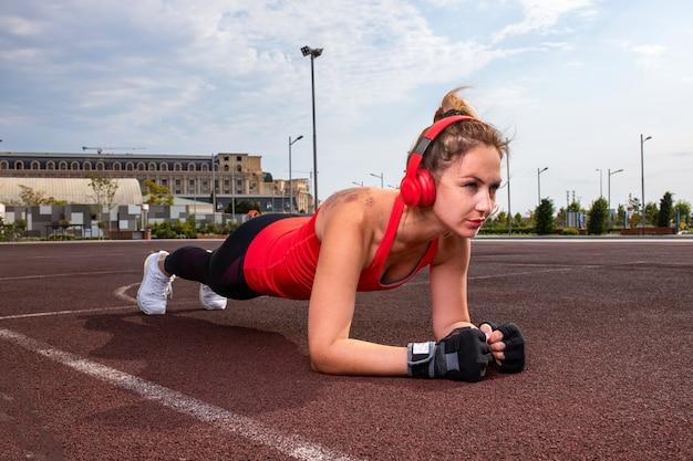 赤いヘッドフォンと体操を行うスポーツ服の女性。