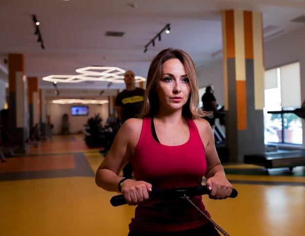 ジムで肩のトレーニングをしているピンクのフィットネス服の女性。