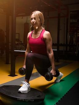 ジムでダンベルと脚のトレーニングを行うピンクの女性。
