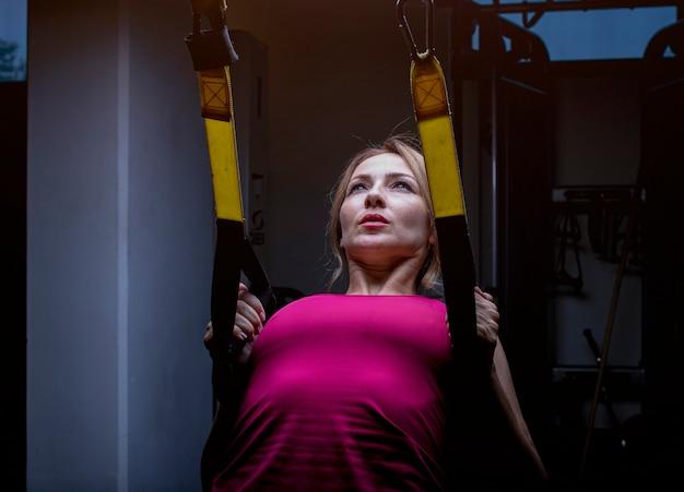 ジムで背中拡張機で背中のトレーニングをしているピンクの女性。